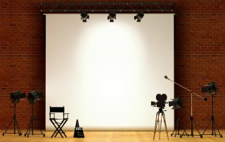 empty stage with chair, screen, and camera