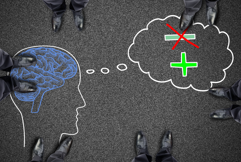 Image of person thinking with negative and positive symbols: negative crossed out