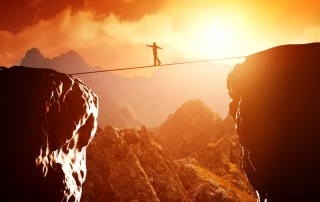 Image of person on a tightrope stretched between two cliffs