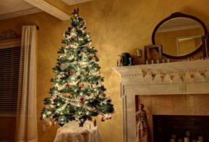 벽난로 옆에 빛나는 크리스마스 트리