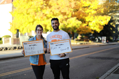two student holding signs thanking you for giving