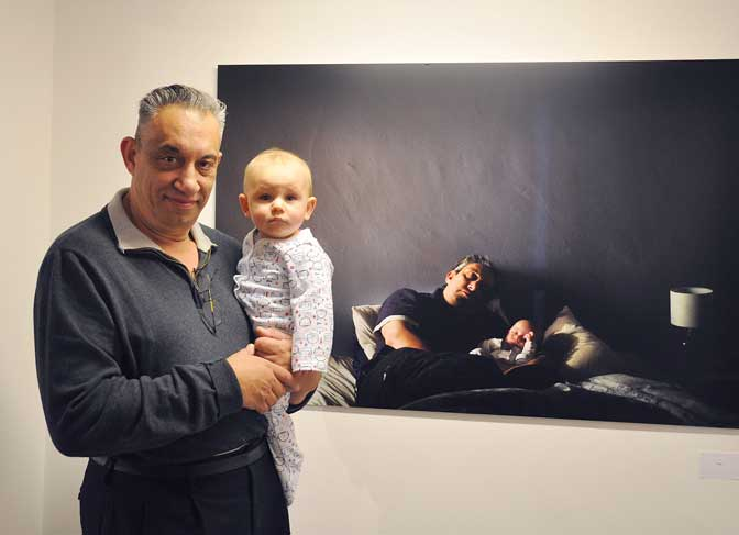The models (Mark Evans and son), behind selected photograph 'Father & Son' by London artist Carole Evans Med