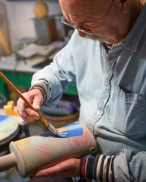 John painting pots. Photo Credit Guy Harris.