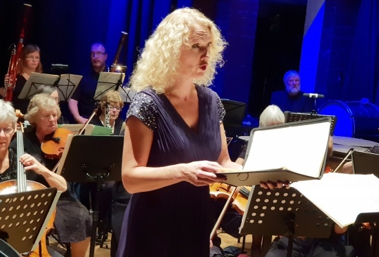Torbay Symphony Orchestra's Catherine Hamilton, a woman in a blue dress holding music, singing in front of an orchestra