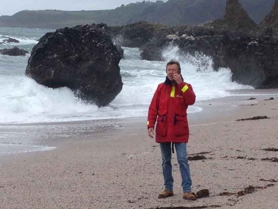 Start Point on the South Hams coastline: artists Chris Elsden is standing on the beachy sand with the foamy sea hitting rocks behind him