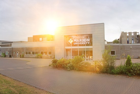 a sun burst sets over the 70s architecture of Plymouth Marjon University main entrance