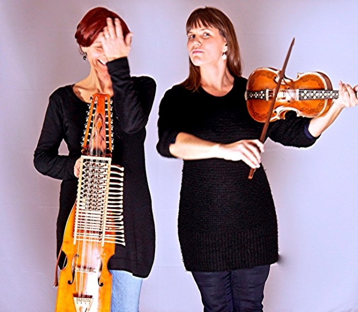 two women are holding strange and ancient instruments
