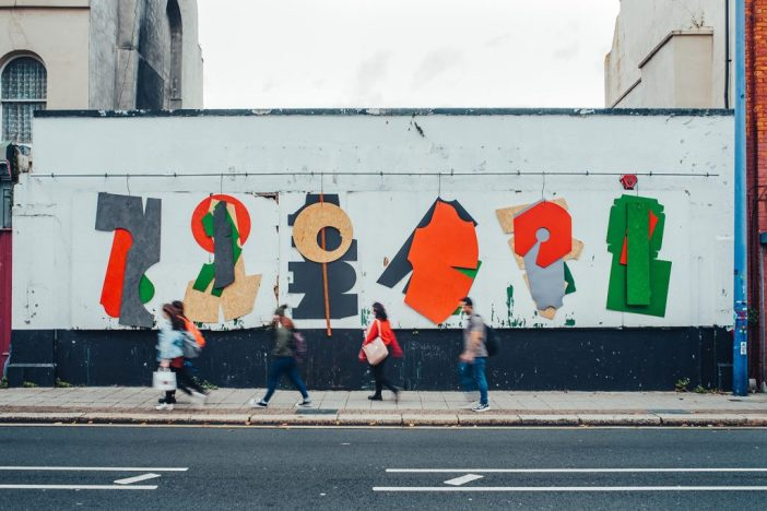 People walking infront of a mural on a borad at Plymouth Art Weekender