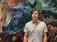 Louis Watts in front of current exhibit by Jennifer Meanly