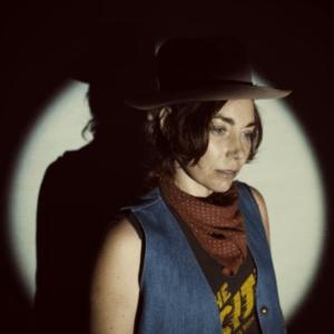 H.C. McEntire in cowboy-esque attire, lit with a spotlight