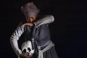 A dancer handling one of the 20 human skulls returned to Namibia following the genocide there. CuePix/Gemma Middleton National Arts Festival 2016
