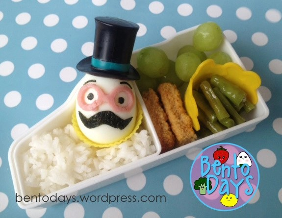 hard boiled eggs, wearing little top hats and mustaches cut out freehand using nori. Glasses cut out using ham.