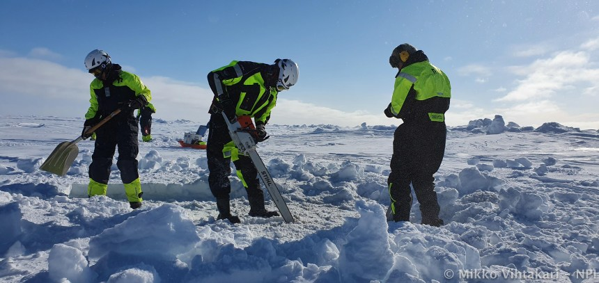 """Amalia, Peter and Haakon making a dive hole in 1.5-meter-thick sea ice in crisp winter weather. On Svalbard, the temperatures are measured by the required clothing. This was a """"balaclava day"""""""