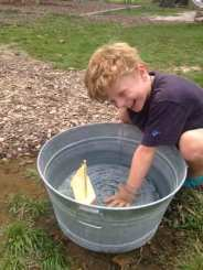 Kindergarten student playing with boat in a bucket. Waldorf Summer