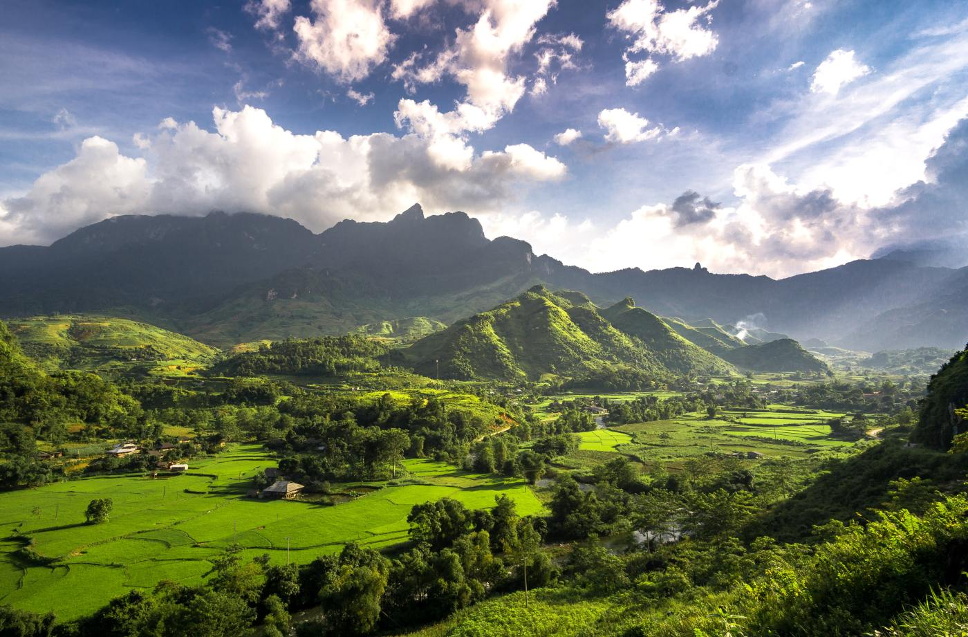 Vibrant fields, mountains, and sparsely clouded, illuminating skies.