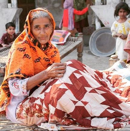 Artisan Aqsa Bibi working on a quilt