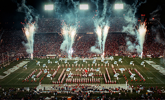 View of the band performing in Bryant-Denny Stadium amid fireworks.