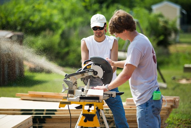 Two men using a power saw