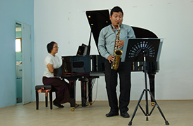 a woman playing piano and a man playing saxophone