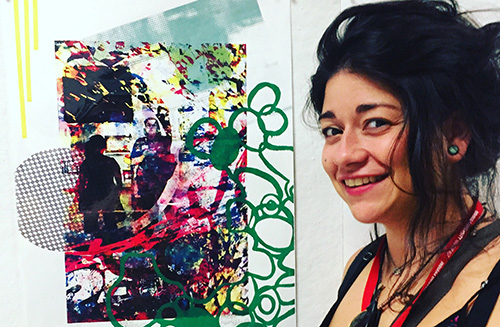 a young woman standing next to one of her art works, a colorful screen print