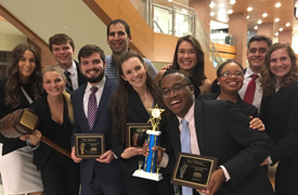 a group of smiling students pose with plaques and an oversized gavel