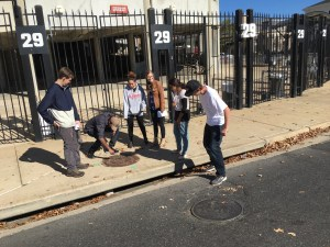 Students looking at drainage outside of the Bryant-Denny stadium.