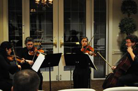 Four musicians sit and perform in the Capstone String Quartet
