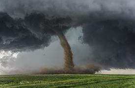tornado touching down on a green field