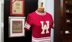 Brenda McCampbell's cheerleading certificate; a newspaper clipping featuring McCampbell; and a vintage cheerleading uniform ca. 1974