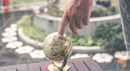 a hand points to a small globe on a patio table