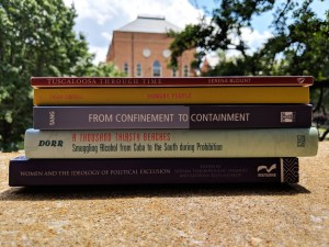 stack of books written by faculty