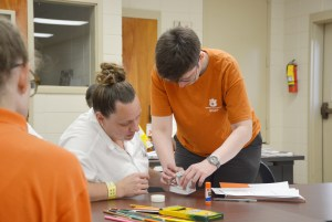 A teacher in the Prison Arts program helps a student participate in the class.