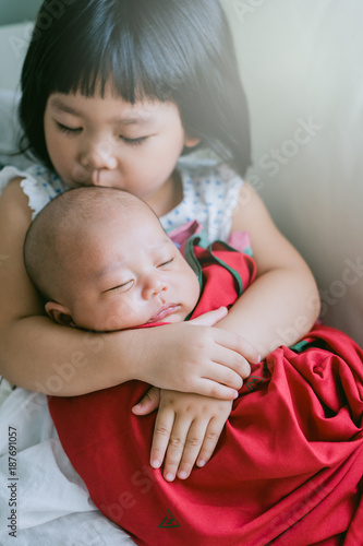 little sister hugging her