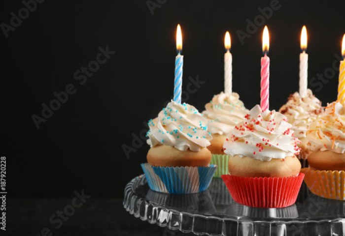 Birthday Cupcakes With Candles On Dessert Stand Against Black