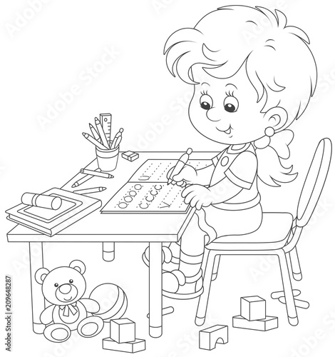 Little girl doing her homework in an exercise book with