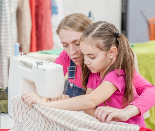 Mom Teaches A Little Girl To Sew On A Sewing Machine