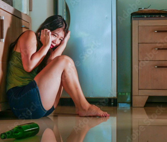 Young Scared Desperate Asian Japanese Woman Crying At Home Kitchen Floor Suffering Domestic Violence And Sexual