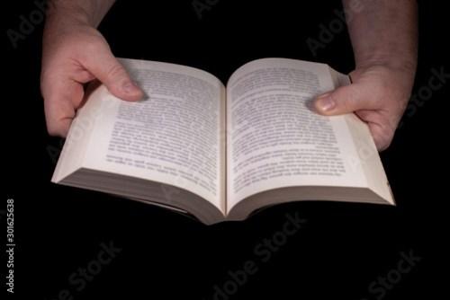 Ein aufgeschlagenes Buch von zwei Händen gehalten vor schwarzem Hintergrund