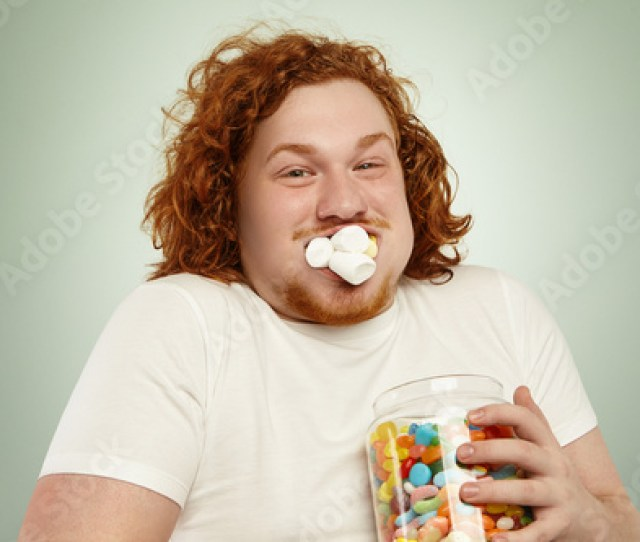 Headshot Of Funny Greedy Fat European Man With Ginger Curly Hair Posing At Studio Holding Glass