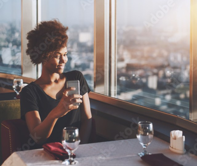 Naughty Curly Afro American Girl Is Sitting In Luxury Cafe On The Top Of Modern Skyscraper And Making Selfie On Frontal Cam Of Her Cell Telephone With Copy