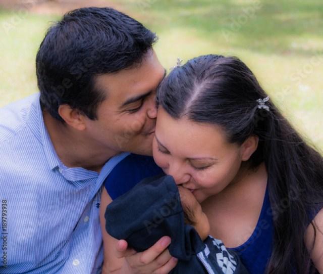 Latino Husband Kisses His Wife While Latina Wife Kisses Her Newborn