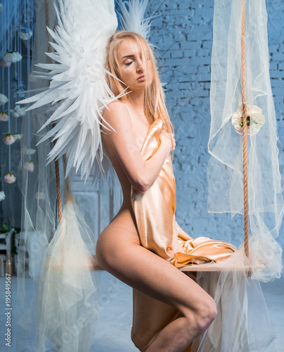 Naked Sexy Girl In White Wings On A Swing In The Studio Posing Hiding A Gold Sheet