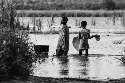 Two girls fetch water from a river in Ayigbekofe in Ghana. This is the main source of water for the people in this community.
