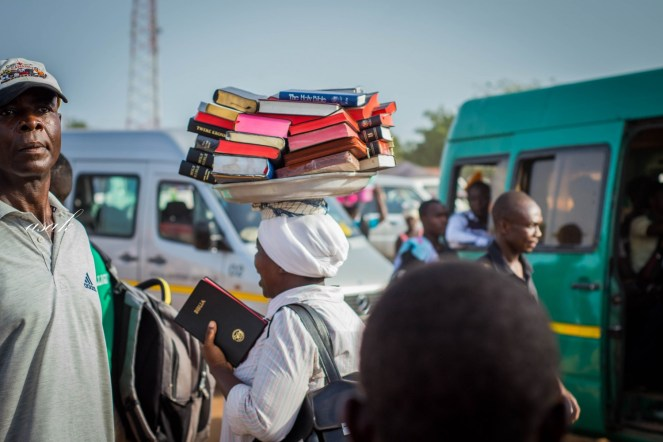 A woman selling bibles at a bus station in Ghana