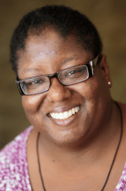 Close up image of Denise Felder in a purple shirt smiling with glasses.