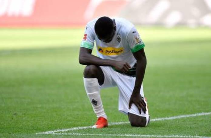 Marcus Thuram knelt on the grass celebrating his goal in the Bundesliga