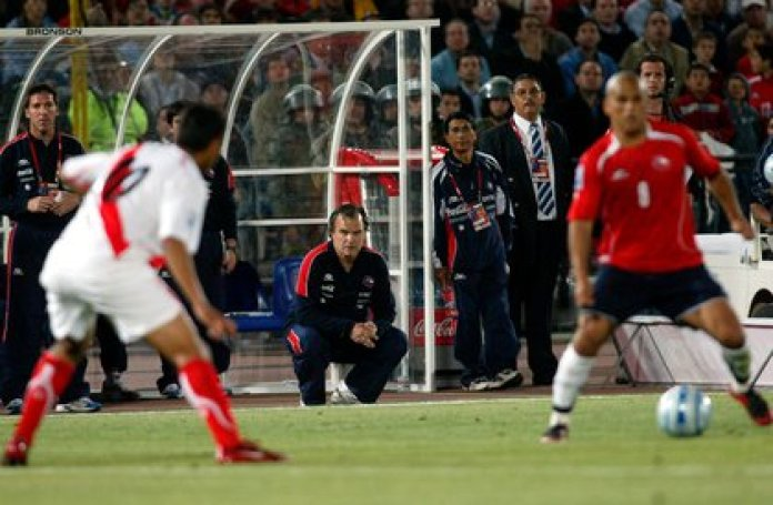 Bielsa squatting and next to his faithful Ladero Cachureo during a match between Chile and Peru for the 2010 Qualifiers (Fotobaires)