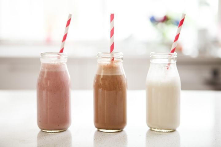 Three cute bottles of different flavoured cashew milk
