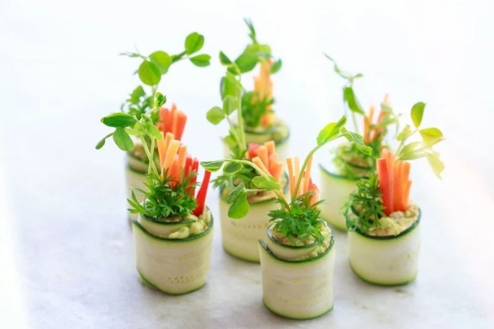 Zucchini roll-ups filled with fresh vegetables and microgreens, ready to serve at a party