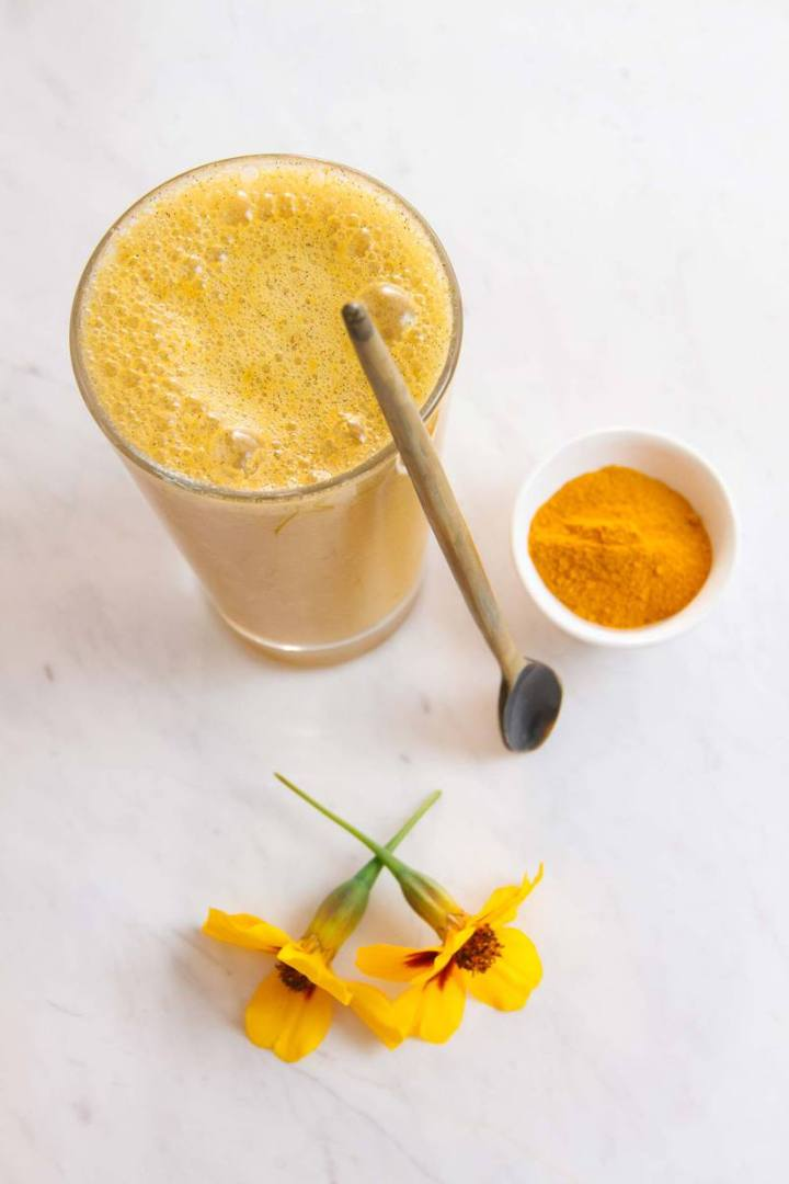 Turmeric smoothie in a glass with a spoon beside it, on the kitchen benech